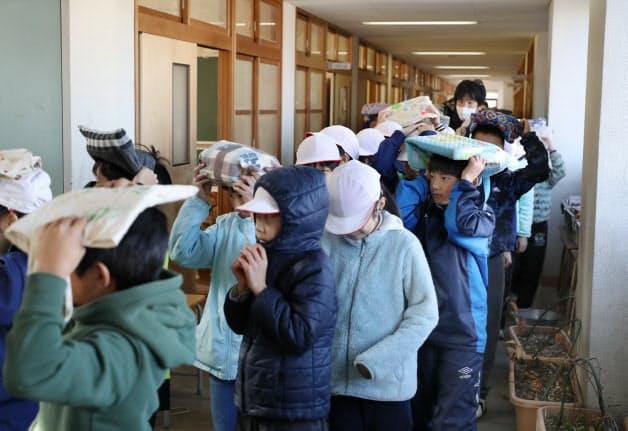 かばんなどで頭を守りながら屋外に避難する児童ら(17日午前、神戸市北区)