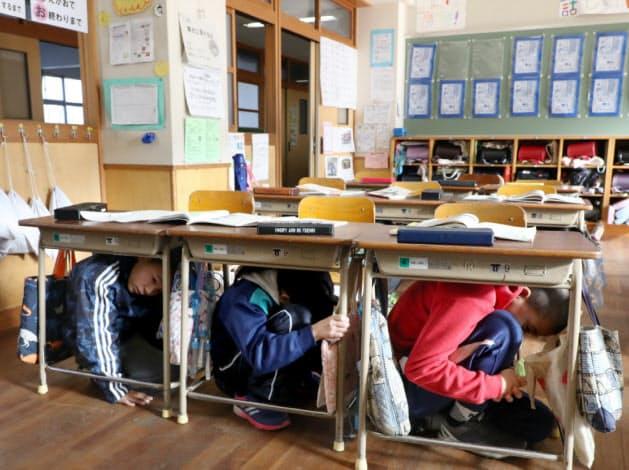 訓練放送と同時に机の下に隠れて姿勢を低くする児童ら(17日午前、神戸市北区)
