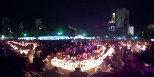 午前5時46分の時報とともに黙とうする人たち(17日、神戸市中央区)=超広角レンズ使用