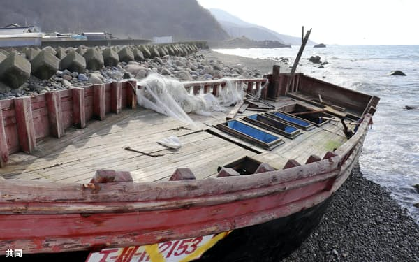 柴田一喜さんの自宅裏に漂着した木造船(2018年12月22日、青森県深浦町)=共同