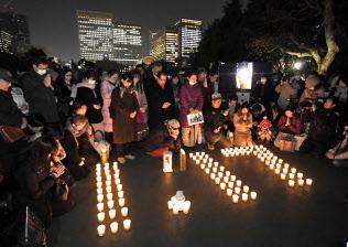 キャンドルにともされ浮かび上がった「1.17」の文字を囲んで黙とうする人たち(17日、東京都千代田区の日比谷公園)