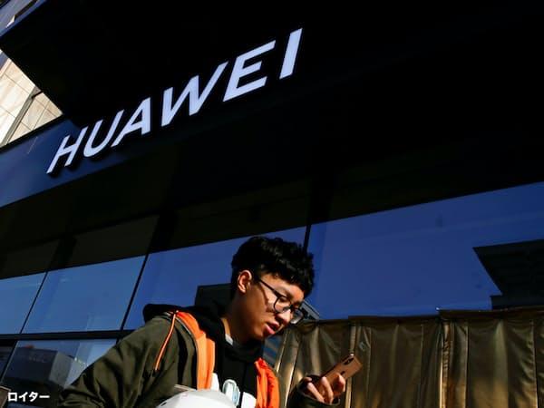 北京にあるファーウェイ製品店舗の前を歩くスマホ利用者=ロイター