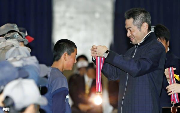 昨年末の「イチロー杯争奪学童軟式野球大会」の表彰式で、子どもたちにメダルをかけるイチロー。23回目の開催だった=共同
