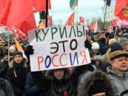 20日、モスクワで開かれた集会で「クリール諸島(北方領土)はロシア領土だ」と書かれた紙を掲げる参加者ら