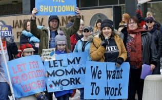 政府機関閉鎖に抗議する人々。政府職員は給与未払いの状態に置かれ、生活費をやり繰りするため消費者金融などに頼り始めている=AP