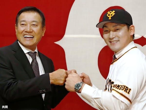 巨人の入団記者会見後に、原辰徳監督(左)とグータッチする丸=共同
