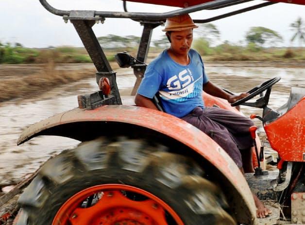 水田を耕すクボタのトラクター。人力や牛に頼ってきた稲作の現場で機械化が進む(バゴー管区)