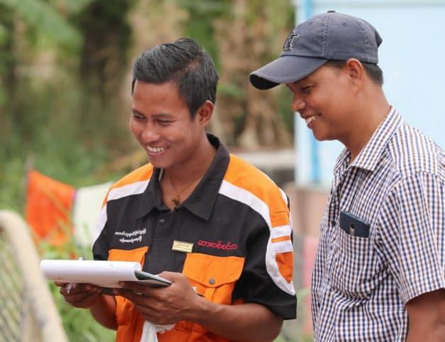 農機のオーナー(右)と話すディーラーの社員。ニーズを細かく聞き取り、サポート体制に力を入れる(バゴー管区)