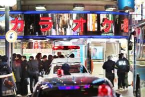 発砲事件が起きたカラオケ店を調べる警視庁の捜査員ら(21日午後、東京都新宿区)
