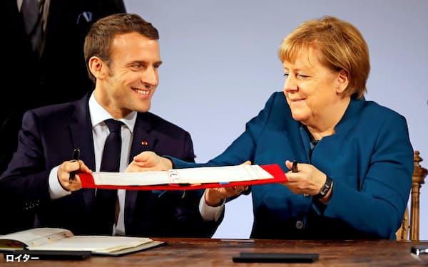 新条約に調印するメルケル独首相(右)とマクロン仏大統領(22日、アーヘン)=ロイター