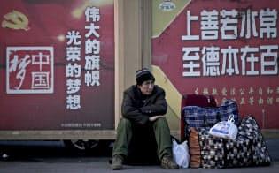 28年ぶりの低成長になった中国の北京駅では出稼ぎ労働者が「中国の夢」の宣伝文の前で荷物を置いて座り込んでいた=AP