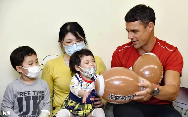 神戸大病院の「こどもセンター」を訪れ、入院患者らと交流する神戸製鋼のダン・カーター選手(24日午前、神戸市)=共同