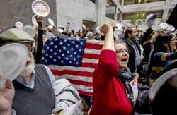 連邦議会議事堂で政府閉鎖に抗議する政府職員ら(23日、ワシントン)=AP