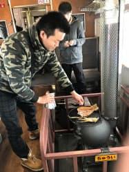 「SL冬の湿原号」の車内。備え付けの石炭式のストーブでスルメをあぶる姿も見られた(26日)