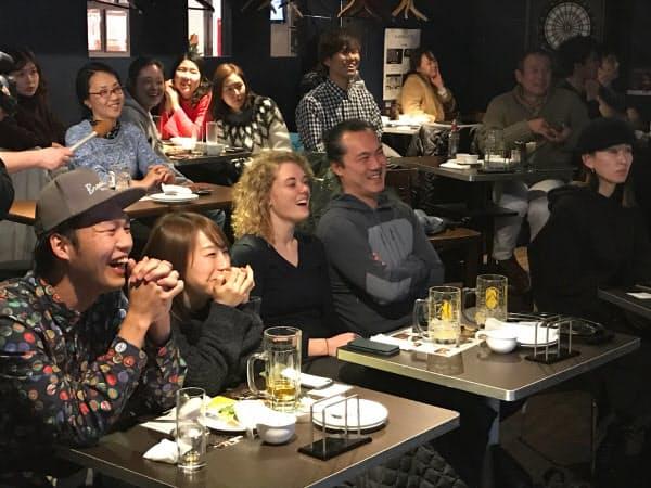 大坂なおみ選手の表彰式インタビューを笑顔で見つめるスポーツバーのテニスファン(26日夜、東京・渋谷)