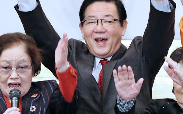 当選が確実になり、万歳する北橋健治氏(27日、北九州市八幡東区)