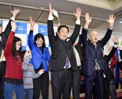 山梨県知事選で初当選を決め、万歳する長崎幸太郎氏(右から2人目)(27日夜、山梨県昭和町)=共同