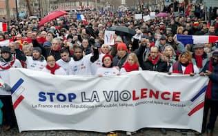 「黄色いベスト」の暴力に反対する「赤いスカーフ」のデモが起きた(27日、パリ)=ロイター