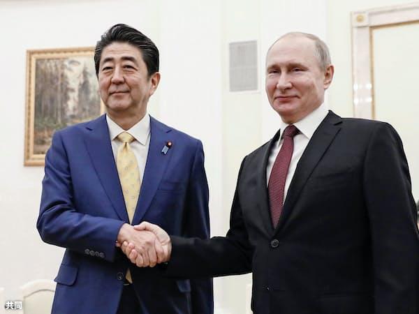 会談前に握手するロシアのプーチン大統領(右)と安倍首相(2019年1月22日、モスクワのクレムリン)=共同