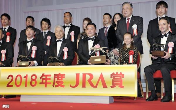 JRA賞授賞式で年度代表馬などに選ばれたアーモンドアイの関係者らと記念写真に納まる騎手大賞を受賞したクリストフ・ルメール騎手=前列右端(28日、東京都内のホテル)=共同