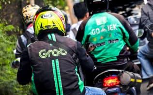 二輪車の配車サービスは東南アジア特有だ(ジャカルタでのグラブ=左=とゴジェックの運転手)=小高顕撮影