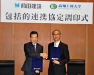 協定を結んで握手する工科大の磯部雅彦学長(右)と前田建設工業の大川氏