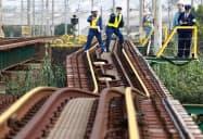 ゆがんだ南海本線の線路を調べる鉄道事故調査官ら(2017年10月、大阪府内)=共同