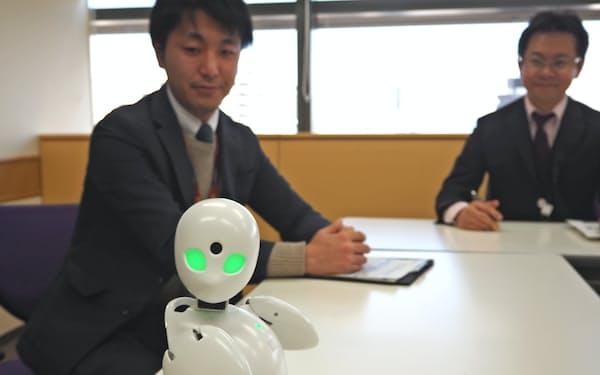 NTT東日本が導入した分身ロボット「OriHime」。社外から操作して職場を見渡したり同僚に話しかけたりできる(東京都新宿区)