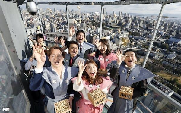通天閣の展望台で豆をまく、三平果歩さん(手前中央)らミュージカル「リトルマーメイド」の出演者(1日午前、大阪市)=共同