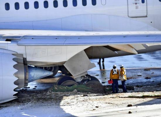 成田空港に着陸後、誘導路で脱輪し動けなくなった日本航空機(1日午前9時48分)=共同