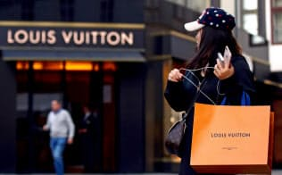 ルイヴィトンの店舗の前で同社の商品袋を携える消費者=ロイター