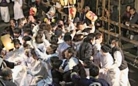 ヤーヤ祭りの「練り」が始まり、集団でぶつかり合う白装束の男たち(2日夜、三重県尾鷲市)=共同