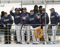 海上での歓迎パレードでファンに手を振る西武の辻監督(左から2人目)と山川(同4人目)ら(3日、宮崎県日南市)=共同