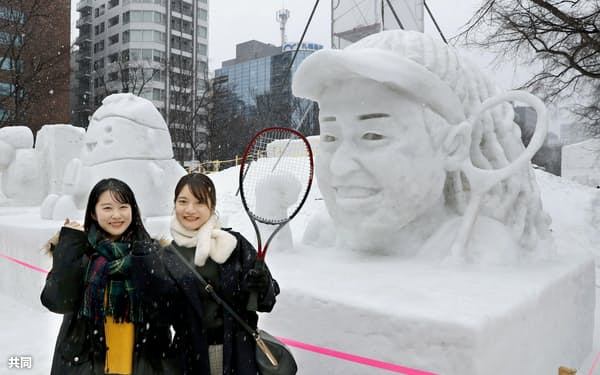 「さっぽろ雪まつり」に登場した、テニスの大坂なおみ選手の雪像の前でポーズをとる観光客(4日午前、札幌・大通公園)=共同
