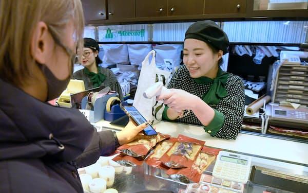 中国系のスマートフォン決済「支付宝(アリペイ)」を使って決済する中国からの観光客(4日午後、大阪市の高島屋大阪店)