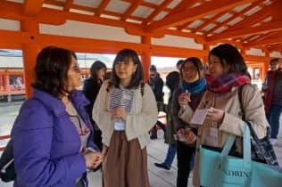 厳島神社で外国人観光客に英語で案内する学生ら