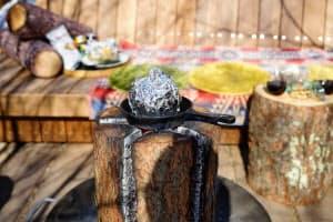 「スウェディッシュトーチ」と呼ばれるたき火でベーコンなどを調理して食べる