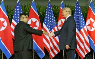 初の首脳会談で握手を交わす北朝鮮の金正恩委員長(左)とトランプ米大統領(2018年6月12日、シンガポール)=AP