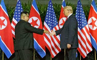 初の首脳会談で握手を交わす北朝鮮の金正恩委員長(左)とトランプ米大統領=2018年6月12日、シンガポール(AP)