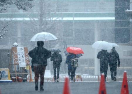 雪が降る中、大学入試の会場に急ぐ受験生ら(9日午前、千葉県習志野市)