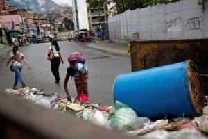 ゴミの中からリサイクル品を探す地元の人(1月、カラカス)=ロイター
