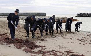 行方不明者の手掛かりを求め、福島県いわき市の砂浜を捜索するいわき東署員ら(8日午前)=共同