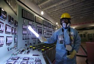 事故発生当時のまま残された3、4号機の中央制御室で計器を見る関係者(12日、福島県大熊町)