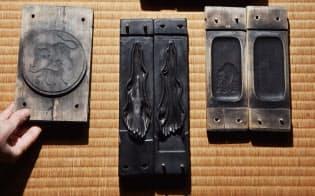 約300年来使い続けている墨の木型。右上から時計回りで「多賀城碑」「香象墨」「蘭奢待」。左側3点は寛政の改革を記念した「丸虎」(奈良市の古梅園)