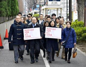 訴状を提出するため、東京地裁に入る原告団ら(14日午前、東京・霞が関)=共同