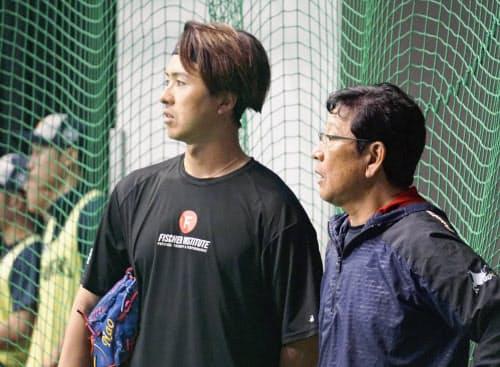 練習を見守る日本ハムの栗山監督=(右)。左は上沢(14日、名護)=共同