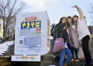 「ペヤングソースやきそば」の巨大オブジェと記念撮影する大学生ら(1日、群馬県渋川市)=共同