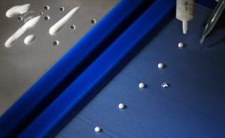 はっ水加工を施したシート(右)をヨーグルトや水が玉になって転がり落ちる。左は未加工のシート