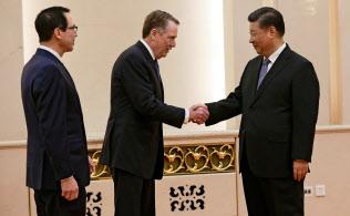 中国の習近平国家主席(右)と握手する米通商代表部のライトハイザー代表(中)(15日、北京)=ロイター