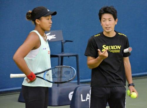 練習の合間に日本テニス協会の吉川真司コーチ(右)と話す大坂なおみ(16日、ドバイ)=共同